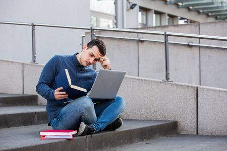 Stressed student preparing for an exam in campus area sitting on university stairs. Student man with laptop, sitting on university stairs. Technology, communication, education and working concept.