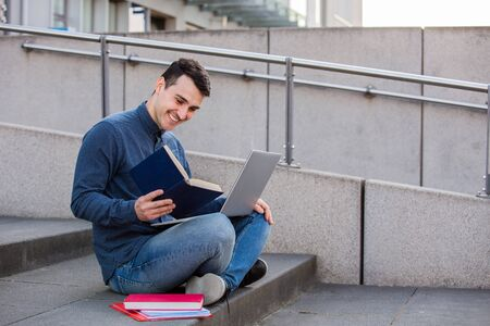 Smiling male student learning for the exam  with a laptop on knees, seated on stairs. Smiling Happy student using laptop and reading book doing his project. Education concept. Banco de Imagens