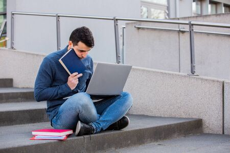 Exhausted Student preparing for an exam in campus area sitting on university stairs.  Stressed Student man with laptop, sitting on university stairs. Technology, communication, education and working concept. Banco de Imagens
