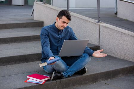 Perplexes student preparing for an exam in campus area sitting on university stairs. Student man with laptop, sitting on university stairs. Technology, communication, education and working concept. Banco de Imagens