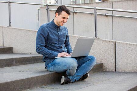University student smiling outdoors using his laptop with free wifi on Campus area sitting on stairs. A confident student holding his laptop over university building background learning for an exam. Banco de Imagens