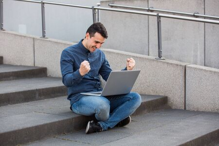 Excited man, with laptop on knees, seated on a stairs raising hands up as celebrating success. Concerned freelancer guy working at his notebook computer, full length.