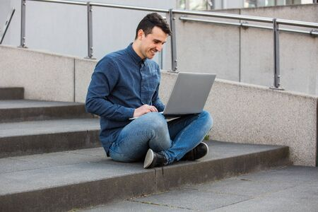 Smiling male student with laptop on knees, seated on a stairs raising hands up as celebrating success. Concerned freelancer guy working at his notebook computer, full length.