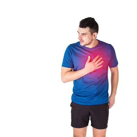 Caucasian man athlete looking aside feeling heart attack or chest pain isolated over white background. Sportsman suffering muscle cramp. Sport traumas, physical injury and healthcare concept. Stock Photo