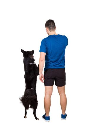 Rear view full length of young man owner training his obedient border collie dog standing on hind paws isolated over white background. Human and pet friendship. Master playing with his puppy.