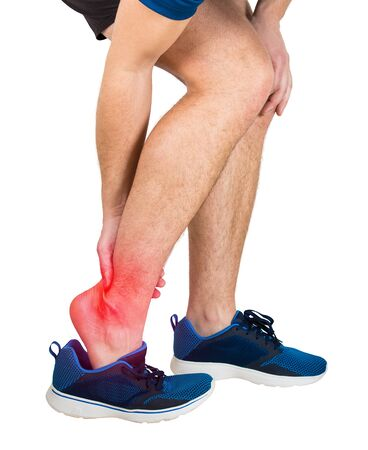 Close up of caucasian man athletic legs feeling ankle pain from exercise isolated over white background. Sportsman suffering muscle cramp. Sport traumas, physical injury and healthcare concept.