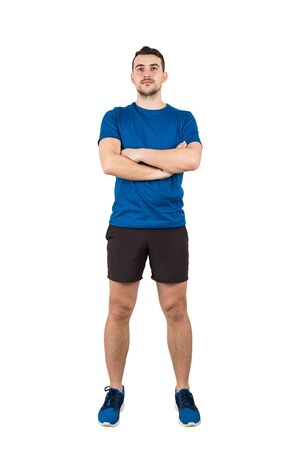 Full length portrait of strong man professional athlete keeps arms crossed, wearing blue t-shirt and black shorts looking confident isolated over white background.