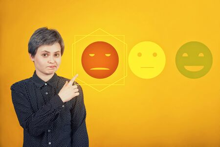 Doubtful skeptical woman pointing forefinger, disappointed face expression, choose negative feedback rating for bad customer service. Press on the sad face emoticon. Dissatisfied client survey symbol.