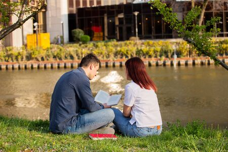 Students learning for exam together in a city park near river. Students Brainstorming Meeting  learning for exam. Fast learning concept. Students Teamwork.