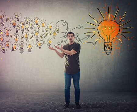 Casual young man, confused face expression, holding hands outstretched as receiving a lot of ideas gathering and create a conclusion. Ingenious student lightbulb education concept. Imagens