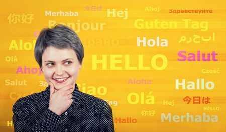 Thoughtful student hipster, happy expression and word hello with different translations on the yellow wall. Multilingual woman learning and speaking many languages. International communication concept Banco de Imagens