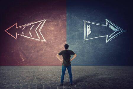 Rückansicht eines zweifelhaften Mannes, Hände auf den Hüften, vor einer geteilten Wand, während die Pfeile auf zwei verschiedene Arten gehen, rote und blaue Seite. Richtige Wahl links oder rechts, Misserfolg oder Erfolg. Schwieriges Entscheidungskonzept.