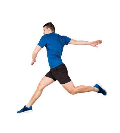 Side vie full length of determined caucasian man athlete jumping over imaginary obstacle isolated over white background. Young guy runner wearing black and blue sportswear makes a leap over chasm. Imagens