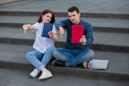 University students with thumb down gesture outdoors on Campus sitting on stairs with books in hand. Exausted students showing thumb down gesture. Learning concept.