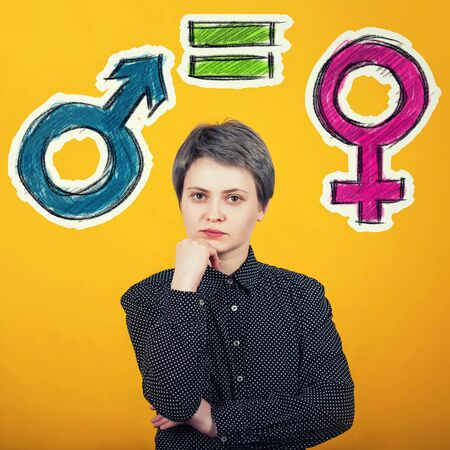 Young woman hipster, short hairstyle, looks with serious expression to camera, thinking of gender equality concept with male and female symbol over yellow wall. Sex sign social issue metaphor.