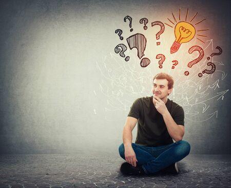 L'uomo pensieroso seduto sul pavimento tenendo la mano sotto il mento ha molte domande come segni di interrogatorio sopra la testa e un'idea brillante come lampadina che brilla attraverso il pasticcio di frecce. Concetto di pensiero geniale.