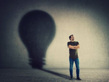 Confident man, keeps arms crossed, casting a lightbulb shape shadow on the wall. Ambition and business idea concept. Motivation and inner power symbol.