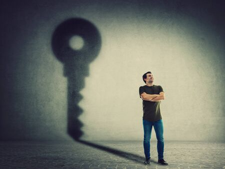Confident man, keeps arms crossed, casting a key shadow on the wall. Ambition and business success concept. Motivation and inner strength symbol.