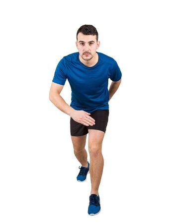 Determined caucasian man runner standing in running position looking ahead confident. Young guy sprinter wearing black and blue sport equipment. Banco de Imagens - 129168276