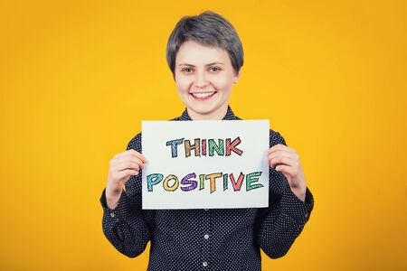 Optimistic extrovert young woman hipster holding a white paper sheet with the message text think positive isolated over yellow background. Colorful motivational slogan, having fun, enjoy the life.
