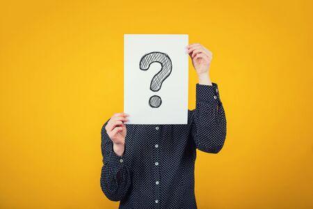 Femme d'affaires couvrant le visage à l'aide d'une feuille de papier blanc avec un point d'interrogation dessiné, comme un masque, pour cacher son identité. Isolé sur fond de mur jaune. Concept d'anonymat féminin introverti.