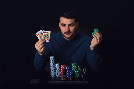 Confident poker player seated at the casino table showing his winning cards over black background. Gambling tournament winner success concept. Chips and dices over dark surface.