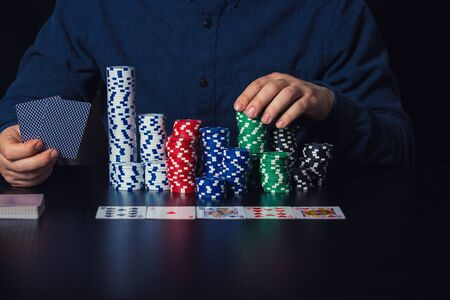 Close up of young man poker player hands holding cards and betting chips at the casino table. Gambling tournament winner success concept over dark background.