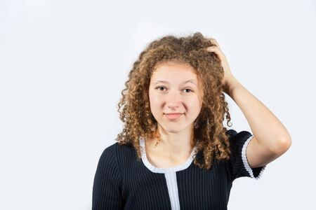 Confused young girl scratching her head looking frustrated over white background. Human facial expression, sign symbol body language.