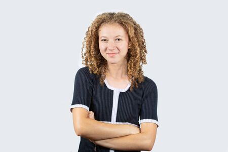 Portrait of happy teenage girl with curly hair smiling looking at camera over grey background.Pretty curly  girl crossed arms smiling and looking at camera.