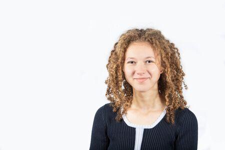 Porträt der glücklichen Jugendlichen mit dem gelockten Haar, das Kamera über grauem Hintergrund lächelt. Hübsches lockiges Mädchen, das Kamera lächelt und betrachtet.