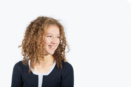 Portrait of happy teenage girl with curly hair smiling looking to left over grey background. Pretty curly girl smiling and looking to something.