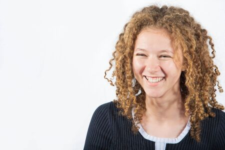Smiling happy teenage girl with curly hair looking to camera over grey background. Cheerful emotion of a curly young girl. Banco de Imagens