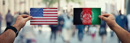 Two hands holding different flags, US vs Afghanistan on politics arena over crowded street background. Diplomacy future strategy, relations between countries. Cooperation or opposite conflict concept Stok Fotoğraf