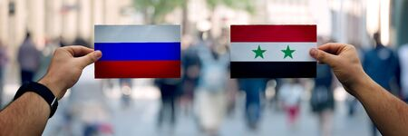 Two hands holding different flags, Russia vs Syria on politics arena over crowded street background. Diplomacy future strategy, relations between countries. Cooperation or opposite conflict concept Stok Fotoğraf