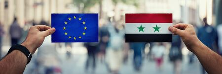 Two hands holding different flags, EU vs Syria on politics arena over crowded street background. Diplomacy future strategy, relations between countries. Cooperation or opposite conflict concept