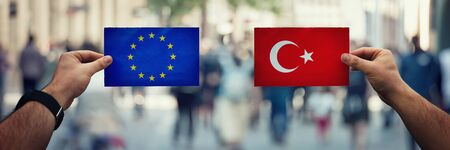 Two hands holding different flags, US vs Turkey on politics arena over crowded street background. Diplomacy future strategy, relations between countries. Cooperation or opposite conflict concept Stok Fotoğraf