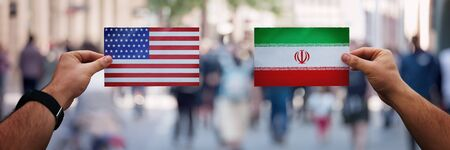 Two hands holding different flags, USA vs Iran on politics arena over crowded street background. Perisan gulf future strategy, relations between countries. Cooperation or opposite conflict concept. Stok Fotoğraf