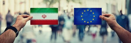 Two hands holding different flags, EU vs Iran on politics arena over crowded street background. Perisan gulf future strategy, relations between countries. Cooperation or opposite conflict concept.