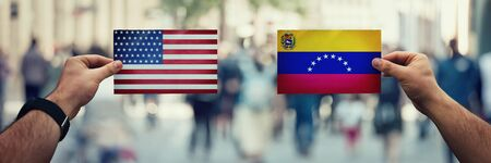 Two hands holding different flags, United States vs Venezuela on politics arena over crowded street background. Future strategy, relations between countries. Cooperation or opposite conflict concept.
