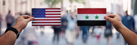 Two hands holding different flags, USA vs Syria on politics arena over crowded street background. Diplomacy future strategy, relations between countries. Cooperation or opposite conflict concept