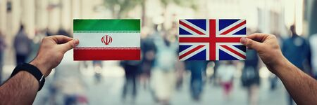 Two hands holding different flags, United Kingdom vs Iran on politics arena over crowded street background. Future strategy, relations between countries. Cooperation or opposite conflict concept.