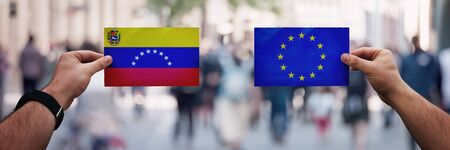 Two hands holding different flags, EU vs Venezuela on politics arena over crowded street background. Future strategy, relations between countries. Cooperation or opposite conflict concept.
