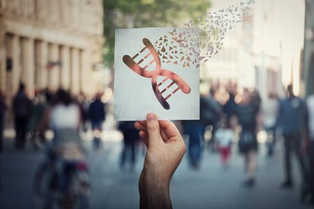 Genetic manipulation and DNA modification concept as human hand holding a paper with gene editing symbol broken into pieces over a crowded street background.