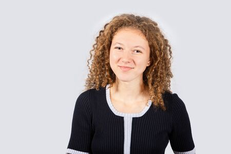 Portrait of happy teenage girl with curly hair smiling looking to camera over grey background. Pretty curly girl smiling and looking to camera.