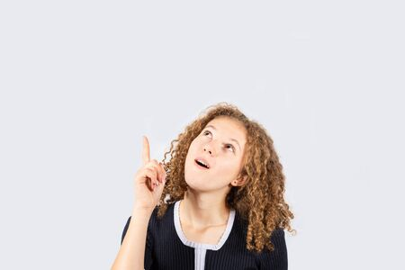 Surprised girl looking and pointing up to something imaginary. Young woman holding her mouth open, shock wow concept. Stunned human emotion isolated on white background.