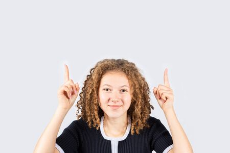 Portrait of happy teenage girl with curly hair smiling looking at camera and pointing up over grey background. Pretty curly girl smiling and looking at camera. Banco de Imagens