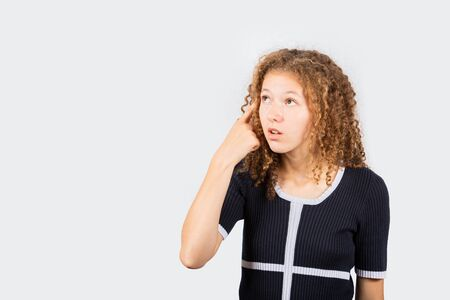 Confused young girl pointing to her head looking frustrated over white background. Human facial expression, sign symbol body language.