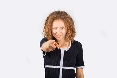 Positive handsome young woman pointing finger to camera isolated over white background. Choice or selection concept.