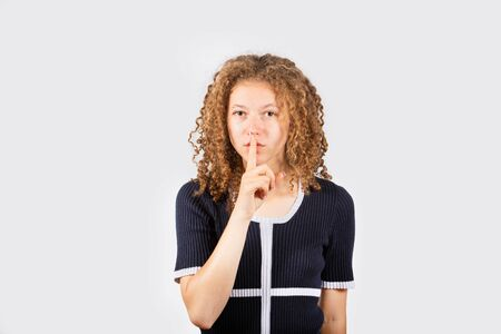 Serious young girl making silence gesture. Pretty girl placing fingers on lips, shhh sign symbol. Conspiracy concept