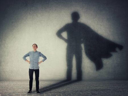 Casual teenage, keeps arms on hips smiling confident, casting a superhero with cape shadow on the wall. Student ambition success concept. Leadership hero power, motivation and inner strength symbol. Banco de Imagens